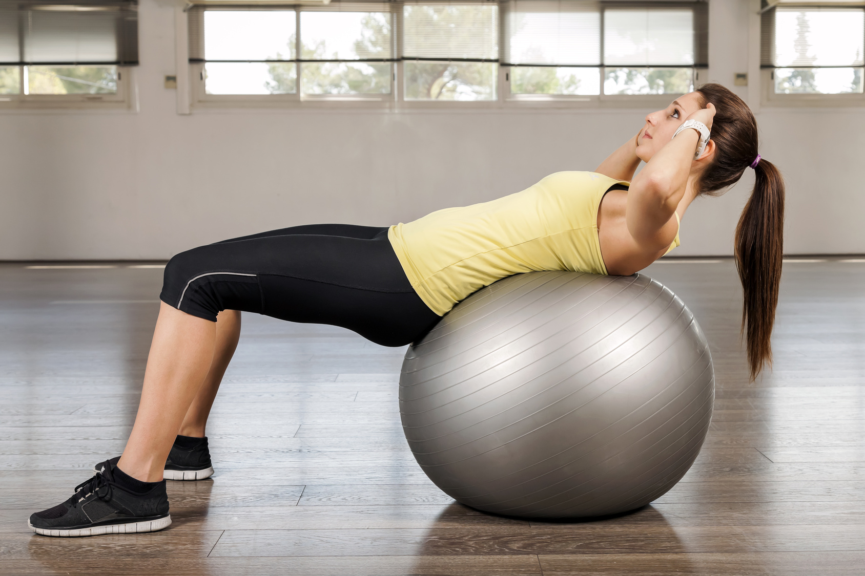 Young woman doing abdominal on a exercise ball